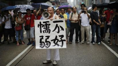 "A man in Mong Kok holds up a sign encouraging democracy protesters, ""Don't be weak."""