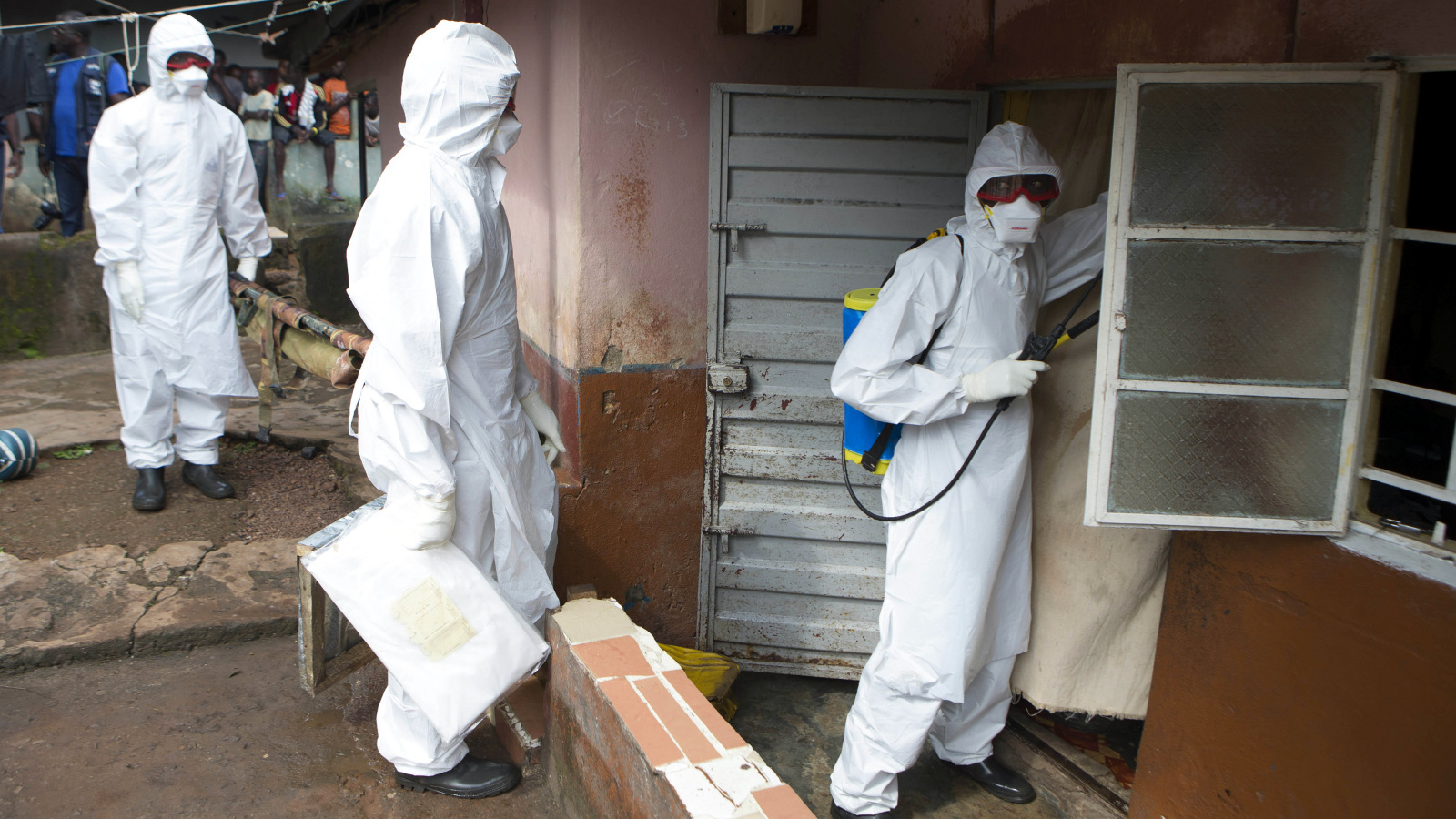 A burial team wearing protective clothing, prepare to enter the home a person suspected of having died of the Ebola virus, in Freetown September 28, 2014.