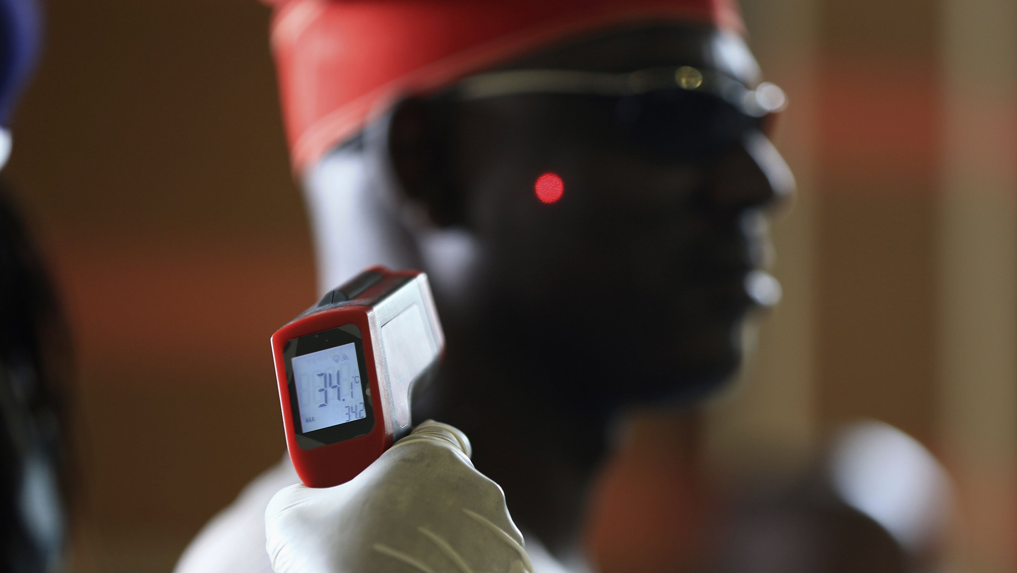 A man has his temperature taken using an infrared digital laser thermometer at the Nnamdi Azikiwe International Airport in Abuja, August 11, 2014. Nigeria's commercial capital Lagos has 10 confirmed cases of Ebola, up from seven at the last count, and two patients have died, including the Liberian who brought the virus in, the health minister said on Monday. REUTERS/Afolabi Sotunde
