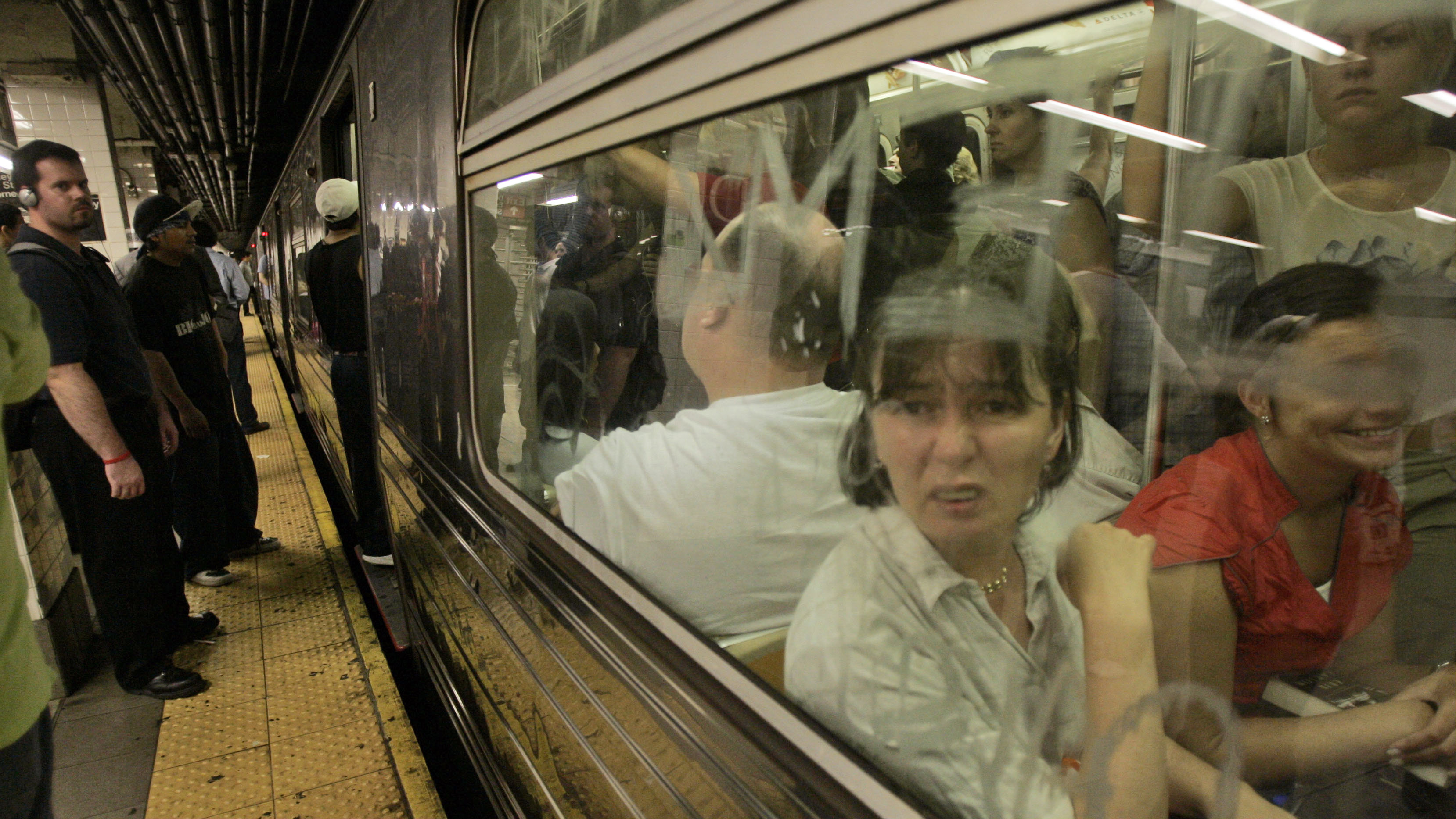 Morning commuters board a crowded uptown F train Wednesday, Aug. 8, 2007 in New York.