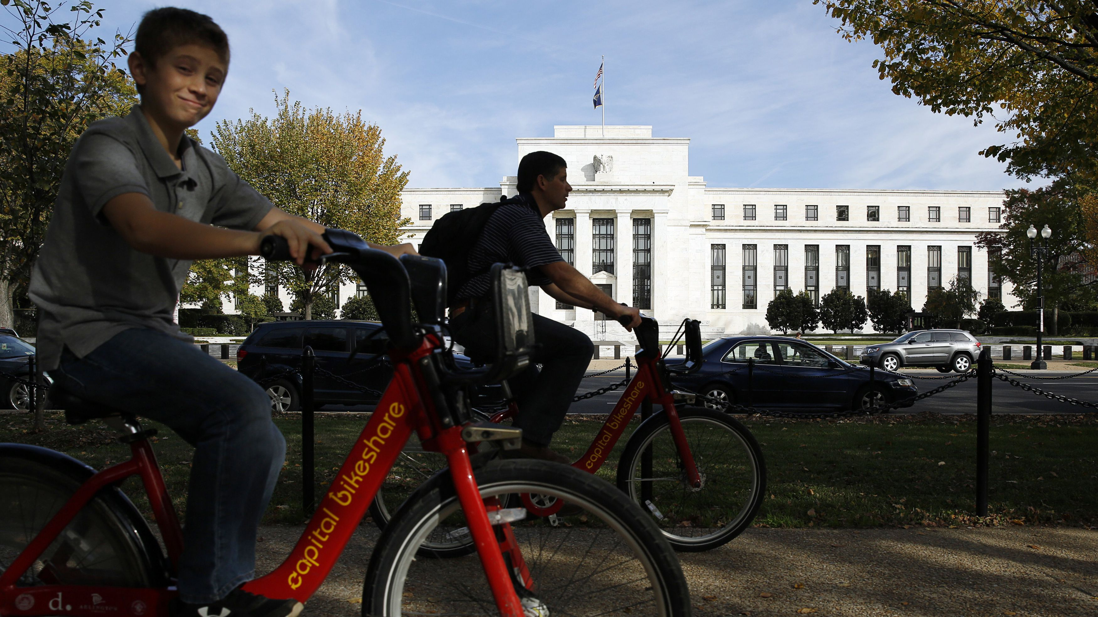 Cyclists peddle past the United States Federal Reserve Board building (rear) in Washington October 28, 2014. The U.S. Federal Reserve this week will likely reinforce its stated willingness to wait a long while before hiking interest rates after a volatile month in financial markets that saw some measure of inflation expectations drop worryingly low. REUTERS/Gary Cameron (UNITED STATES - Tags: BUSINESS POLITICS)
