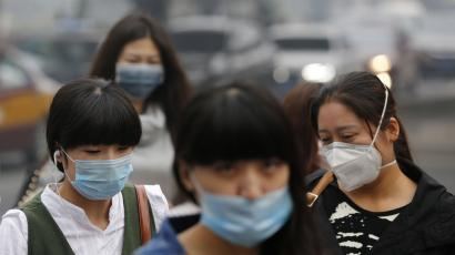 Pedestrians wearing masks walk on a street during a hazy day in Beijing October 10, 2014. Widespread smog has affected a large part of north China including capital Beijing as the National Meteorological Center (NMC) extended a yellow alert on Thursday for air pollution, Xinhua News Agency reported.
