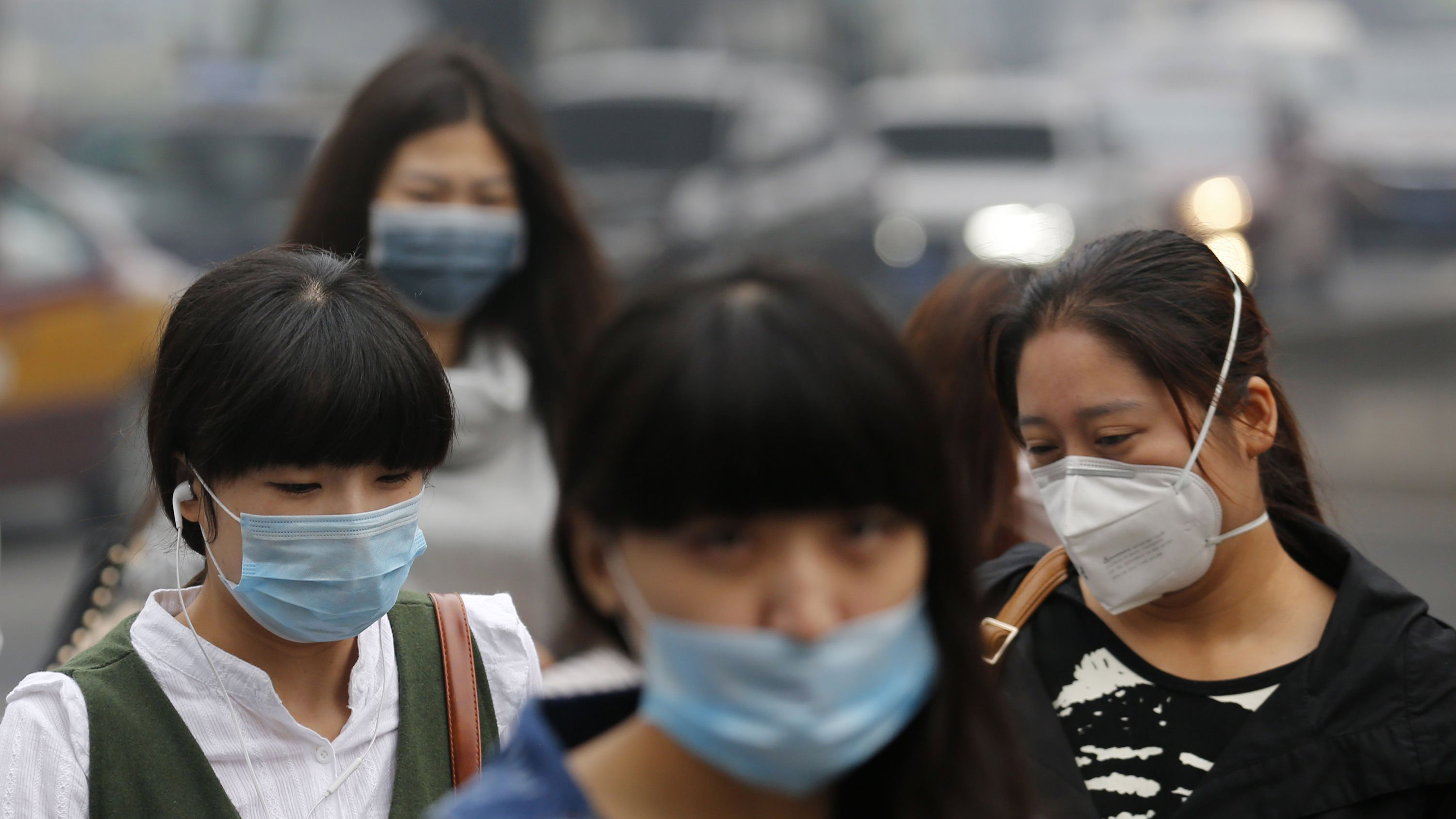 Pedestrians wearing masks walk on a street during a hazy day in Beijing October 10, 2014. Widespread smog has affected a large part of north China including capital Beijing as the National Meteorological Center (NMC) extended a yellow alert on Thursday for air pollution, Xinhua News Agency reported.  REUTERS/Kim Kyung-Hoon