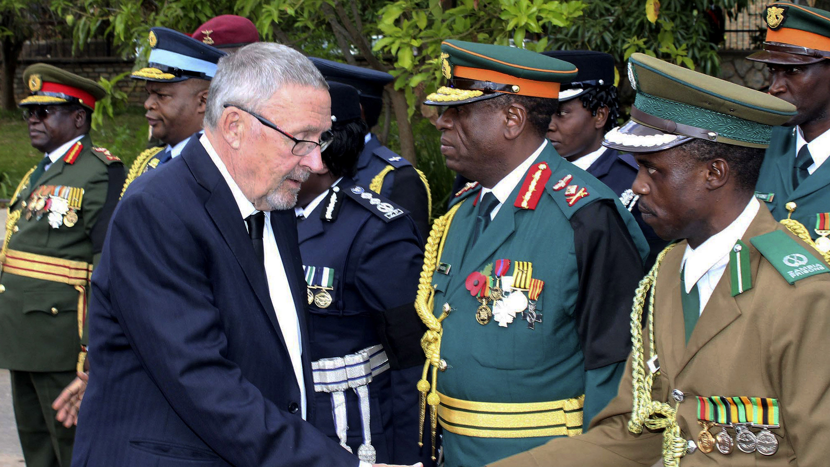 Zambia's vice president Guy Scott greets defense and security chiefs shortly after taking over as acting president, following the death in London on late Tuesday of President Michael Sata, Lusaka, Wednesday, Oct. 29, 2014. Scott, a white Zambian of Scottish descent, became the country's acting president on Wednesday, making him the first white leader of a sub-Saharan African nation since F.W. de Klerk, the apartheid-era head of South Africa who was voted out of power in 1994.