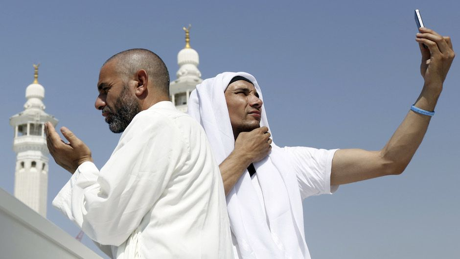 A Muslim pilgrim prays as another takes a photo with his mobile phone at the Grand Mosque on the last day of the annual haj pilgrimage in Mecca