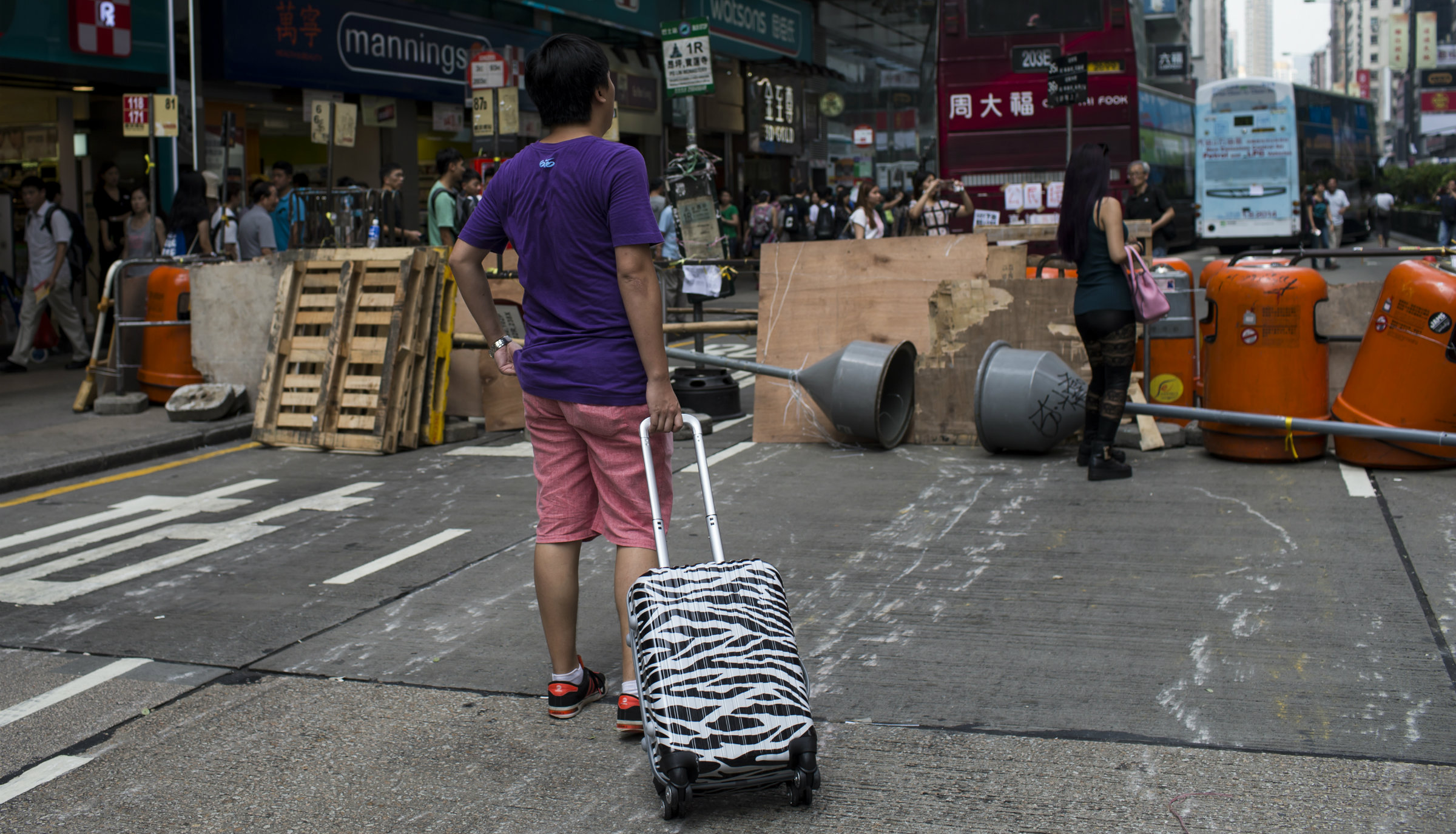 A tourist with a rolling suitcase stands in front of protest barricades in Hong Kong.