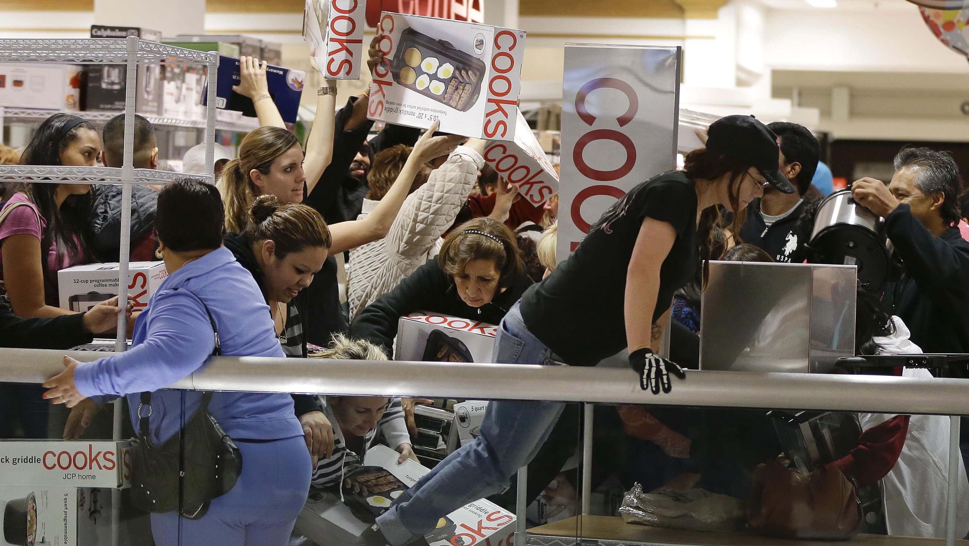 Shoppers rush to grab electric griddles and slow cookers on sale for $8 shortly after the doors opened at a J.C. Penney story, Friday, Nov. 23, 2012, in Las Vegas.