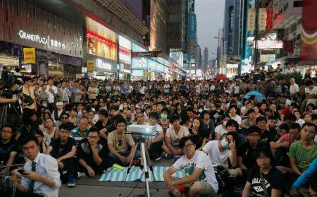 Hundreds of pro-democracy protesters watch a live broadcast of a meeting between student leaders and government officials on a road blocked by them at Mongkok shopping district in Hong Kong October 21, 2014. REUTERS/Bobby Yip (CHINA - Tags: POLITICS BUSINESS EDUCATION) - RTR4AYMR