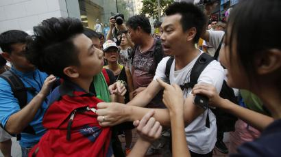 A pro-democracy student protester, left, is pressed by angry locals trying to remove the barricades blocking streets in Causeway Bay, Hong Kong, Friday, Oct. 3, 2014.