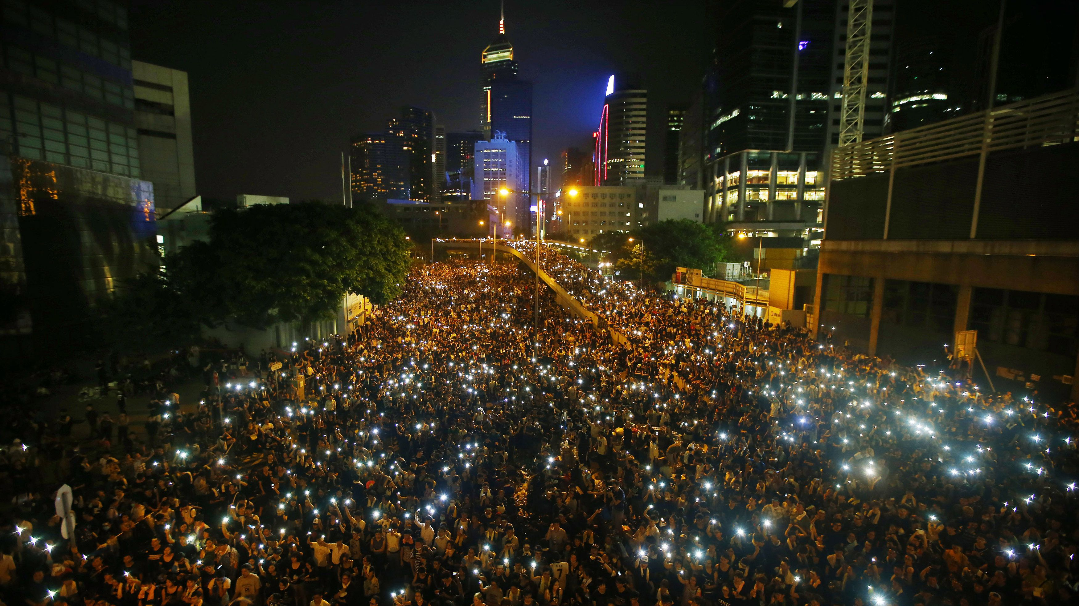 Protesters hold their mobile phones as they block the main street to the financial Central district, outside the government headquarters, in Hong Kong September 29, 2014.