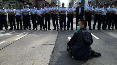 A pro-democracy protester sits in front of a line of policemen on a blocked road at Mongkok shopping district in Hong Kong.
