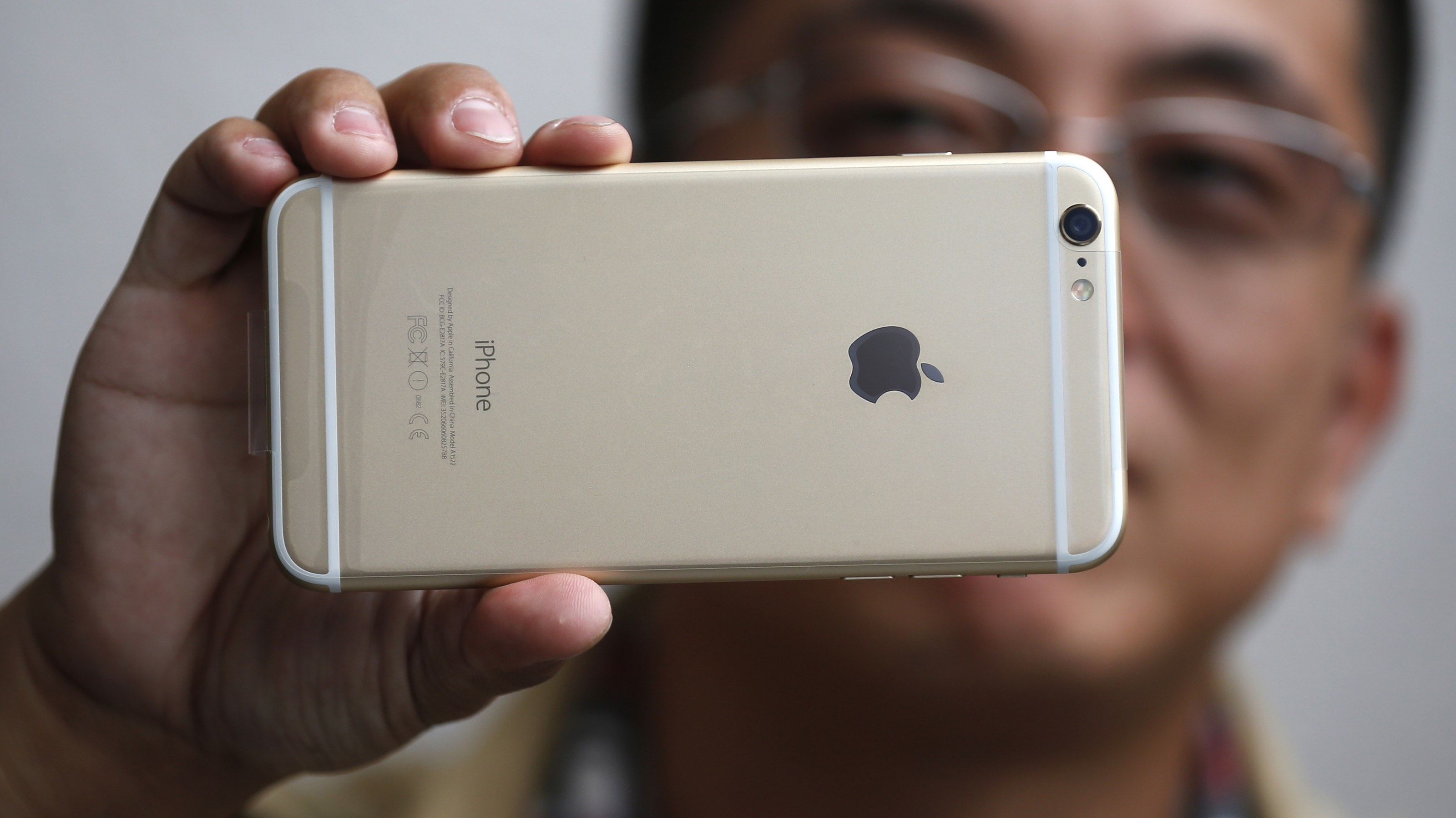 Tony Zhan, 32, holds up his new iPhone 6 Plus after it went on sale at the Apple store in Pasadena, California September 19, 2014. Hundreds of customers waited in lines outside the store on the first day the new iPhone became available. REUTERS/Lucy Nicholson (UNITED STATES - Tags: BUSINESS TELECOMS)