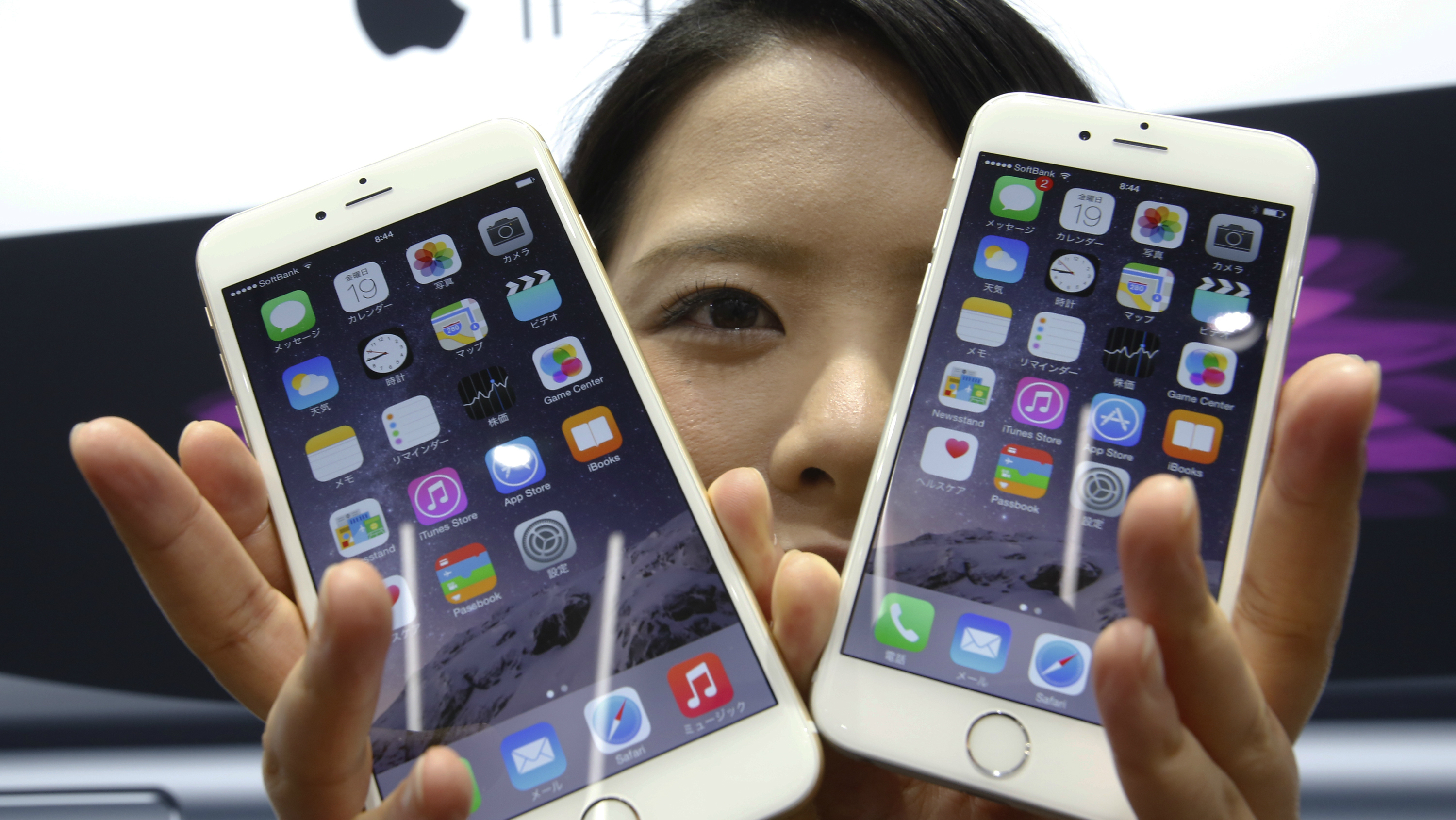 A customer shows off the new Apple iPhone 6 and 6 Plus at a store in Tokyo Friday, Sept. 19, 2014. (AP Photo/Shizuo Kambayashi)