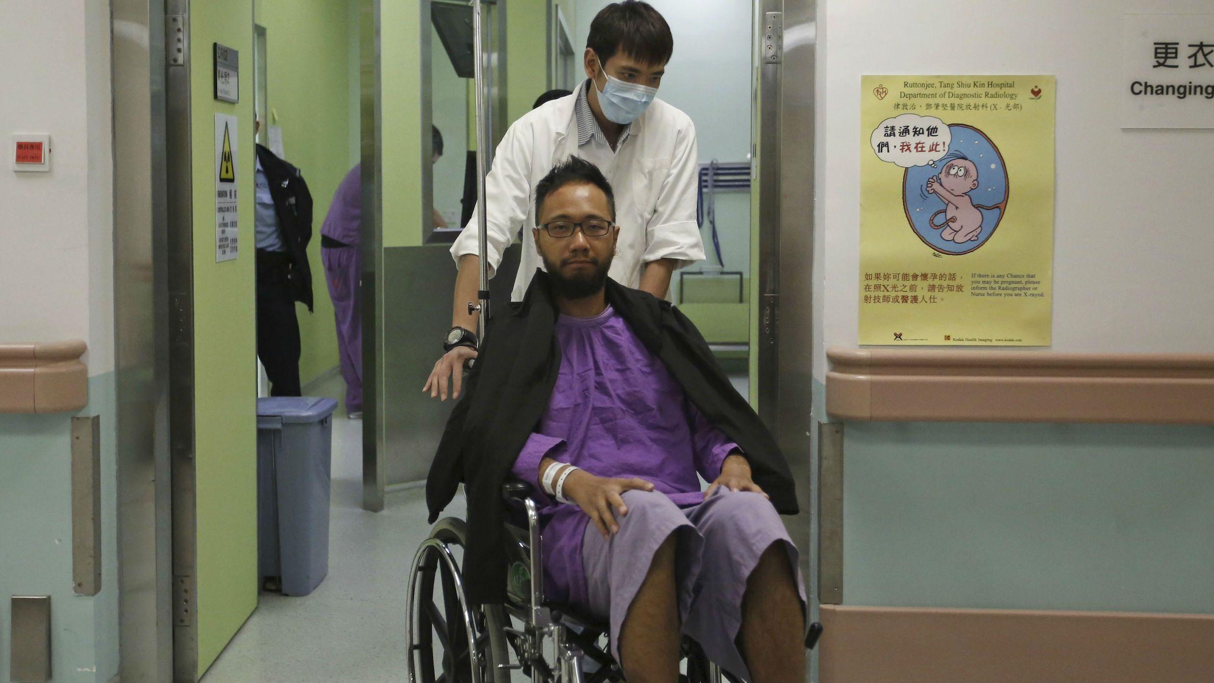 A hospital staff pushes Ken Tsang Kin-chiu on a wheelchair for a medical examination at Ruttonjee Hospital in Hong Kong