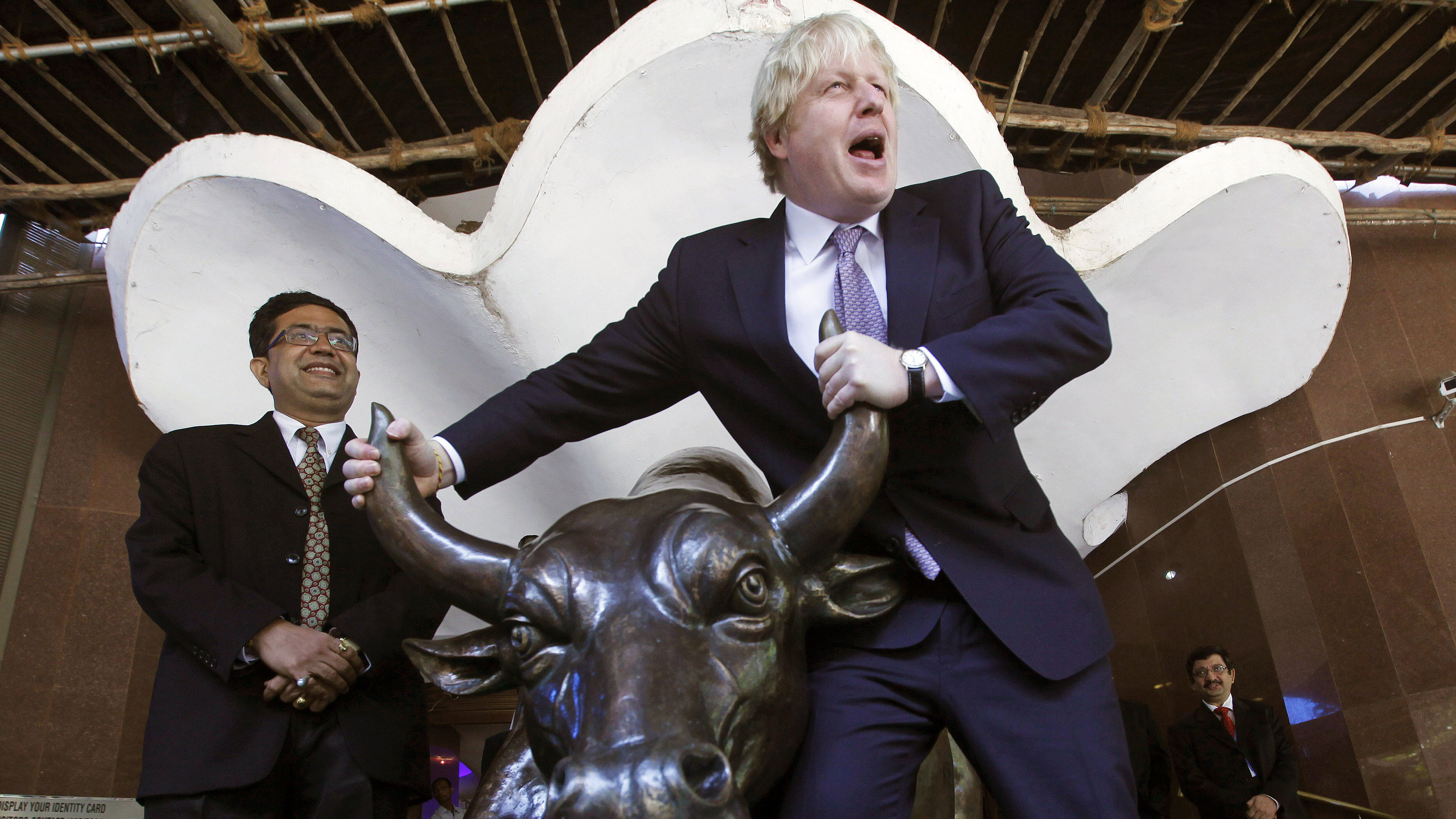 Mayor of London Boris Johnson poses with the bronze statue of a bull outside the Bombay Stock Exchange (BSE) after the launch of new carbon market index at an event in Mumbai, India, Friday, Nov. 30, 2012. Johnson is in India to promote London as the destination of choice for investors and international trade, according to press release.