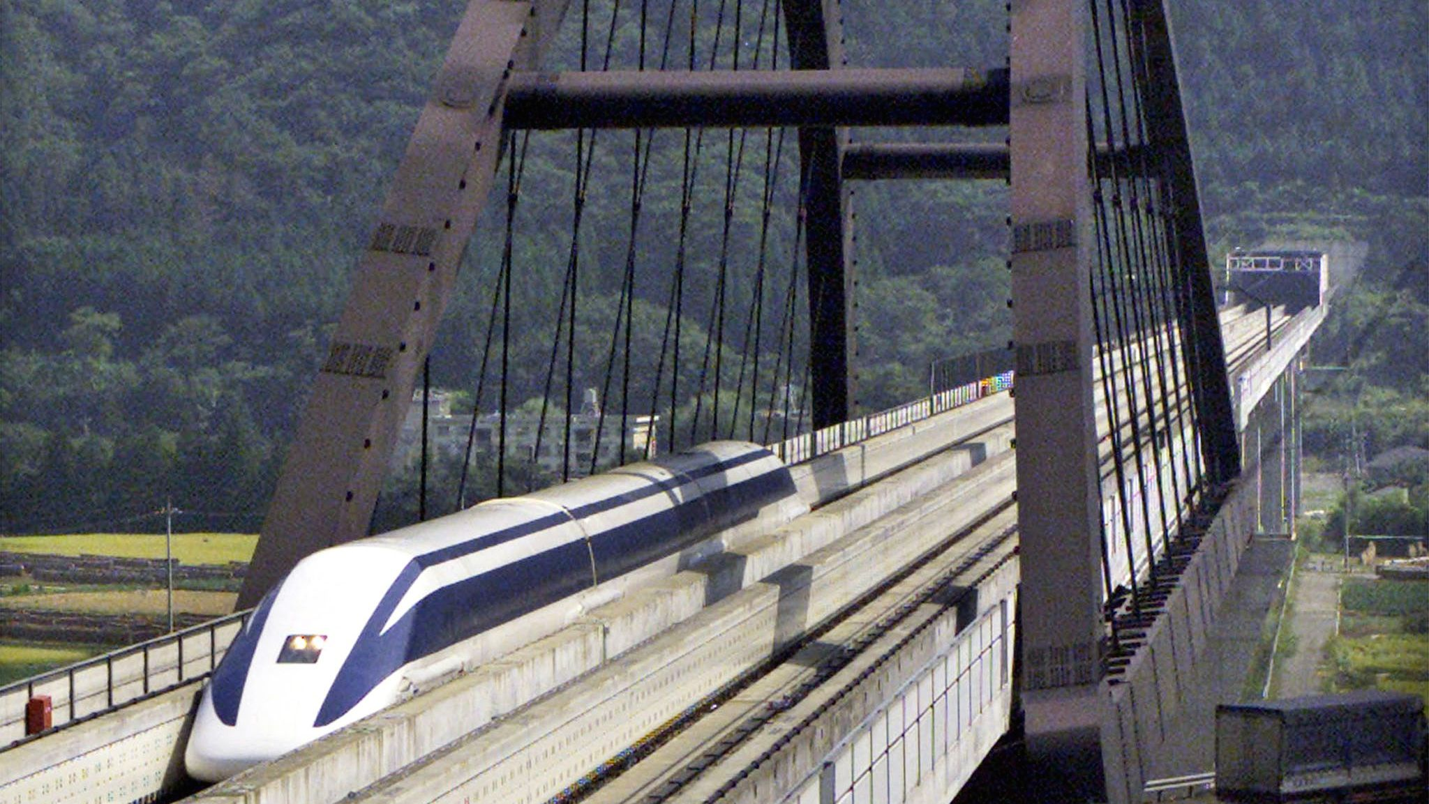 Japan's superconducting linear motor Maglev runs on a railway bridge during a test run on the Maglev Test Line in Yamanashi September 20, 2000. Maglev, the Superconducting Magnetically Levitated Transport System, ran at a speed of 450 kilometres (281 miles) per hour on the test track. The maximum speed for a train transportation system, 552 km/h, was recorded in April last year with a five-car manned vehicle, and received a Guinness World Record Certificate. The ultra-high speed linear motor Maglev is expected to link Tokyo and Osaka in about one hour by running at a speed of 500 km/h.