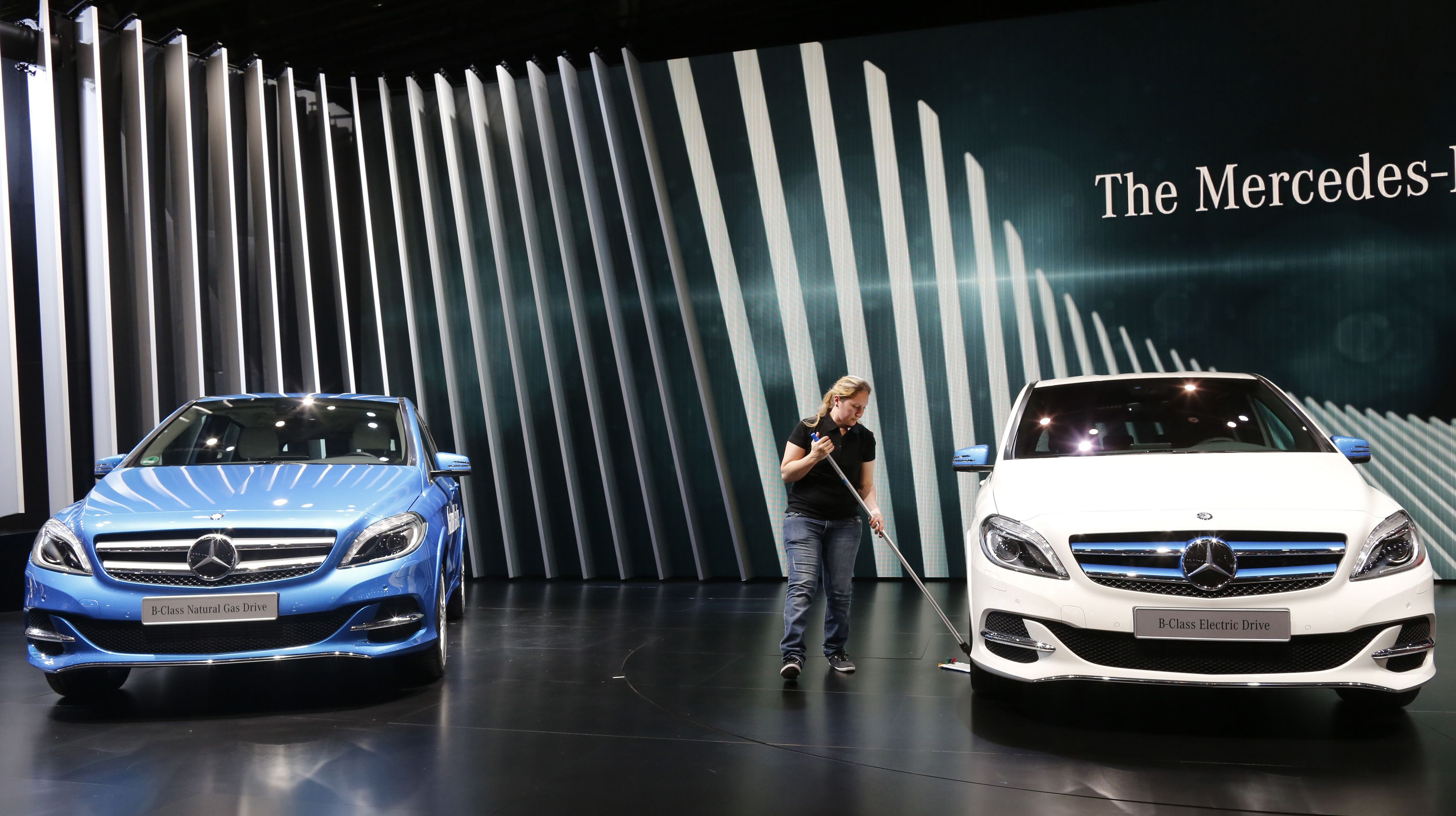 A woman cleans near Mercedes-Benz cars before a news conference on media day at the Paris Mondial de l'Automobile, October 2, 2014. The Paris auto show opens its doors to the public from October 4 to October 19.