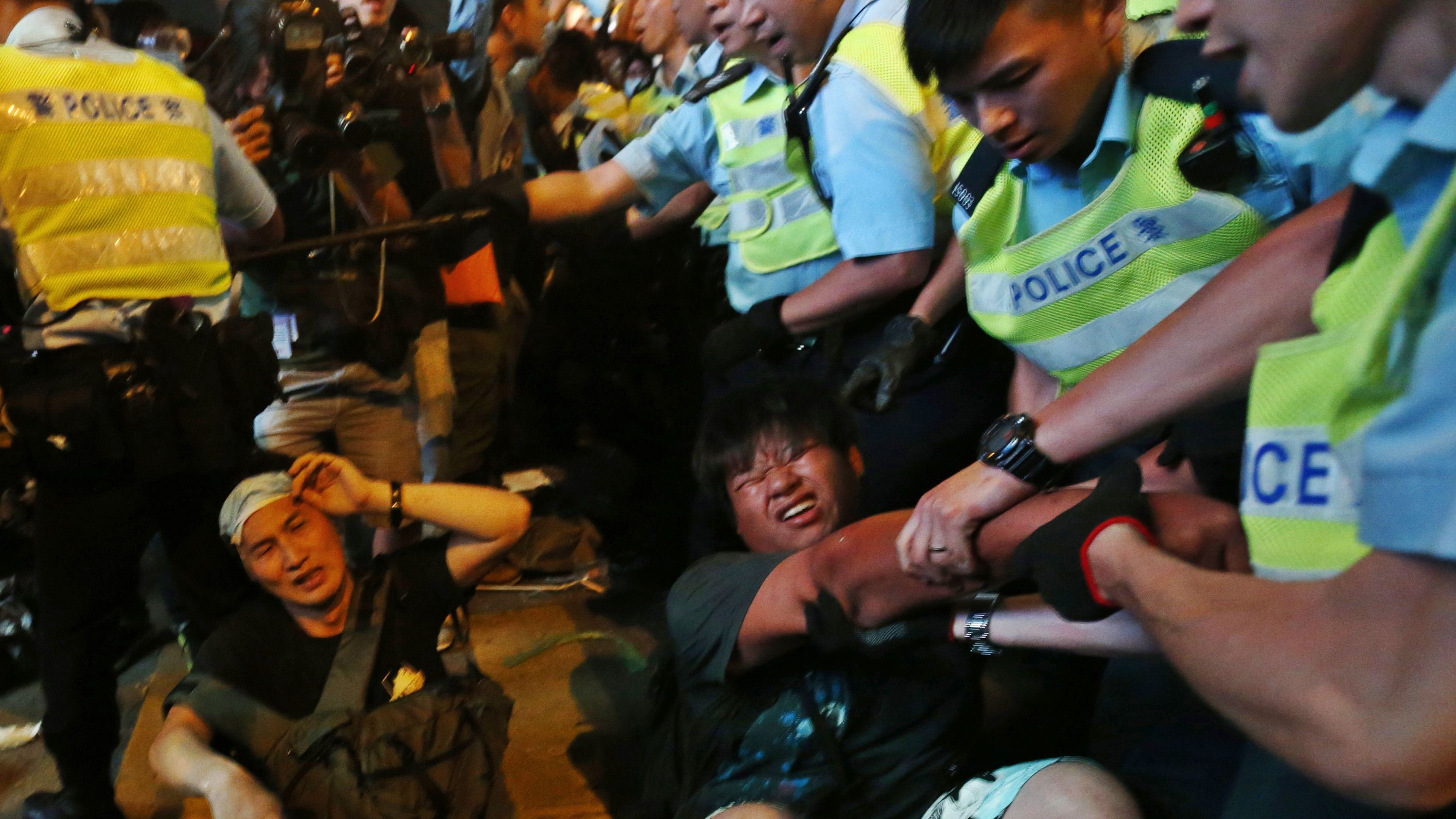 Protesters are dragged away by riot police during a confrontation at Mongkok shopping district in Hong Kong October 17, 2014. Hong Kong riot police used pepper spray and baton charged crowds of pro-democracy protesters on Friday evening as tension escalated after a pre-dawn clearance of a major protest zone in the Chinese-controlled financial hub. REUTERS/Bobby Yip