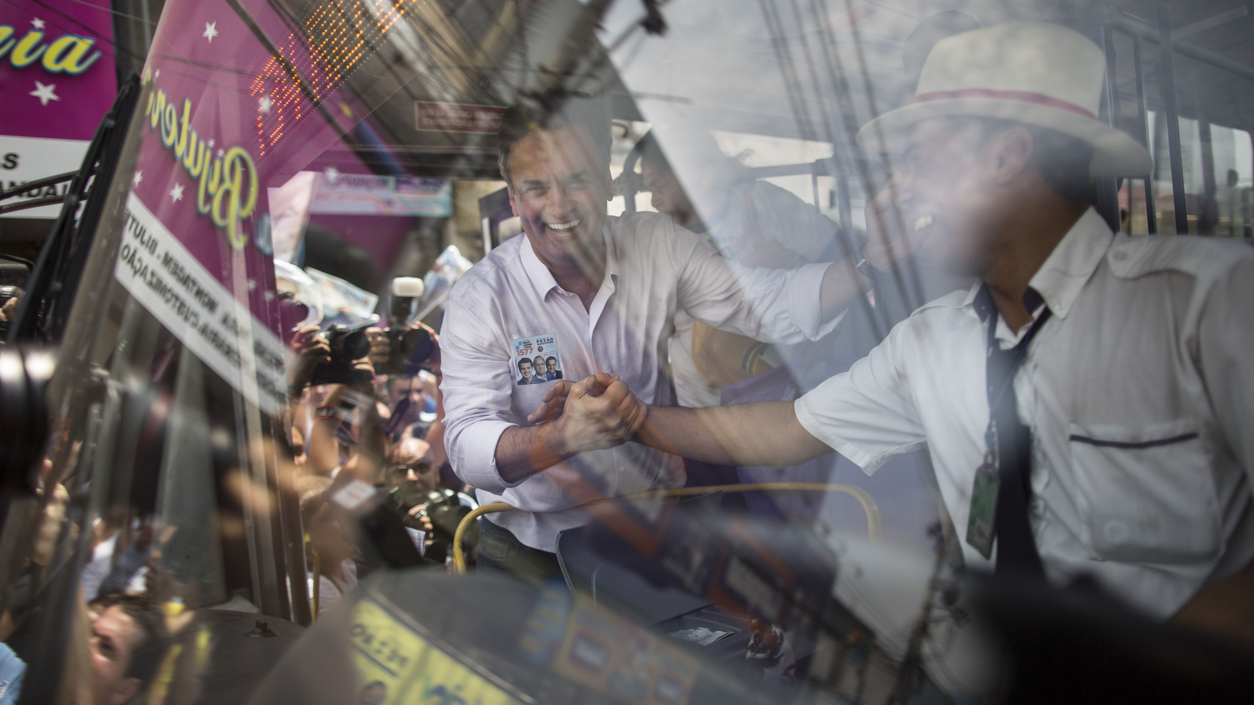 """In this Tuesday, Sept. 30, 2014 photo, Aecio Neves, presidential candidate of the Brazilian Social Democracy Party, PSDB, greets a bus driver outside the """"Mercadao de Madureira,"""" or Madureira Market in Rio de Janeiro, Brazil. Official results showed Sunday that President Dilma Rousseff will face Neves in a second-round vote in Brazil's most unpredictable presidential election since the nation's return to democracy nearly three decades ago. (AP Photo/Felipe Dana)"""