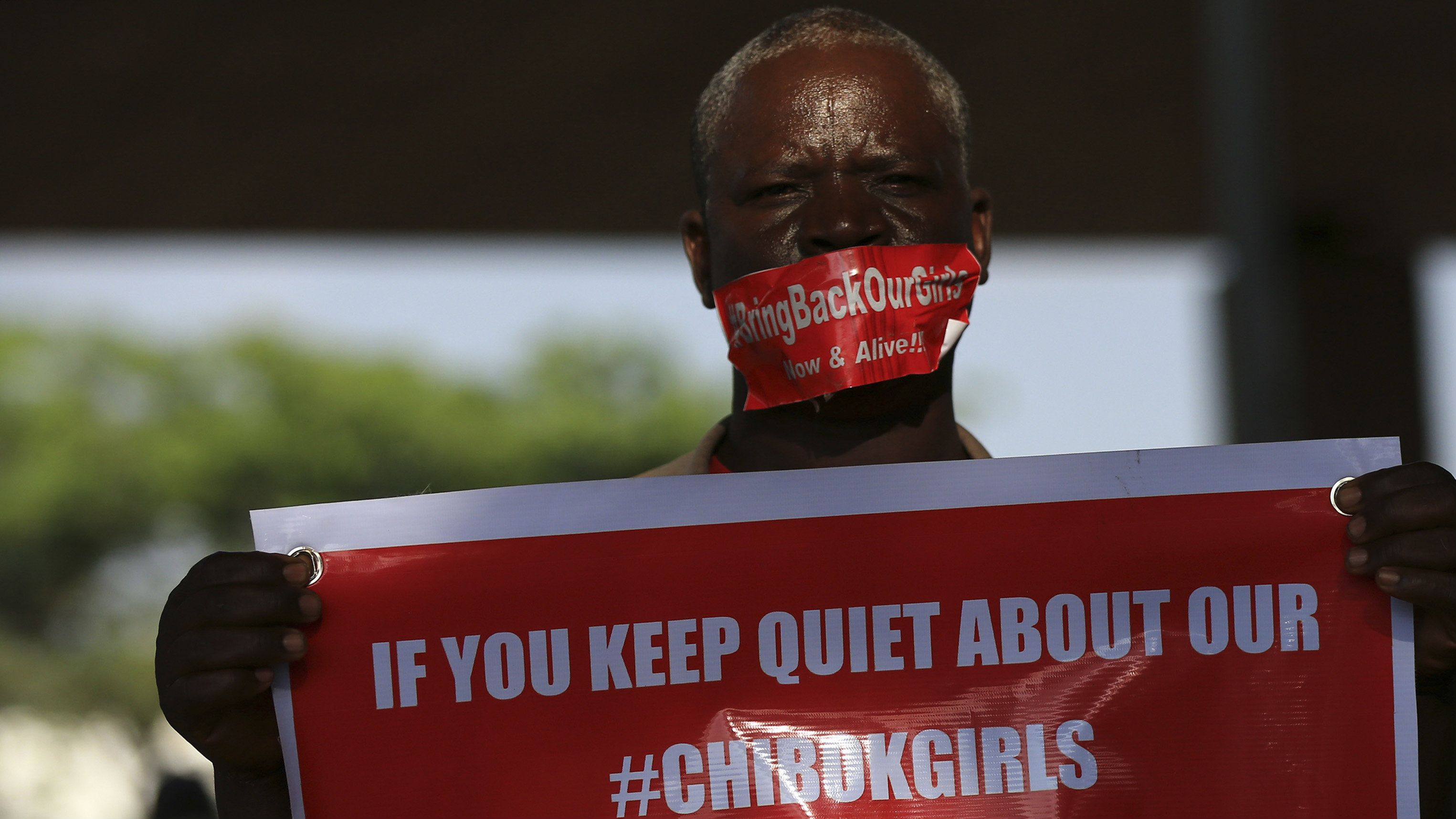 A member of the #BringBackOurGirls campaign group holds a placard under a bridge on the 140th day of the abduction of 219 schoolgirls from Government Secondary School in Chibok, Borno State, while they were sitting for their final exams, during a protest in Abuja September 1, 2014. Picture taken September 1, 2014.