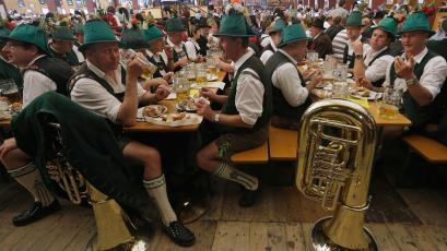 "Participants of the Oktoberfest folklore parade eat and drink in a beer tent at the famous Bavarian ""Oktoberfest"" beer festival in Munich, southern Germany, Sunday, Sept. 23, 2012. The world's largest beer festival, to be held from Sept. 22 to Oct. 7, 2012 will see some million visitors. (AP Photo/Matthias Schrader)"