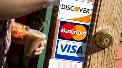 A coffee shop displays signs for Visa, MasterCard and Discover, in Washington, May 1, 2013. MasterCard Inc, the world's second-largest payment network, reported a higher-than-expected rise in quarterly profit, but the company's revenue missed analysts' estimates as a sluggish global economy weighs on consumer spending. Visa Inc reported a higher-than-expected quarterly profit as people spent more with cards.