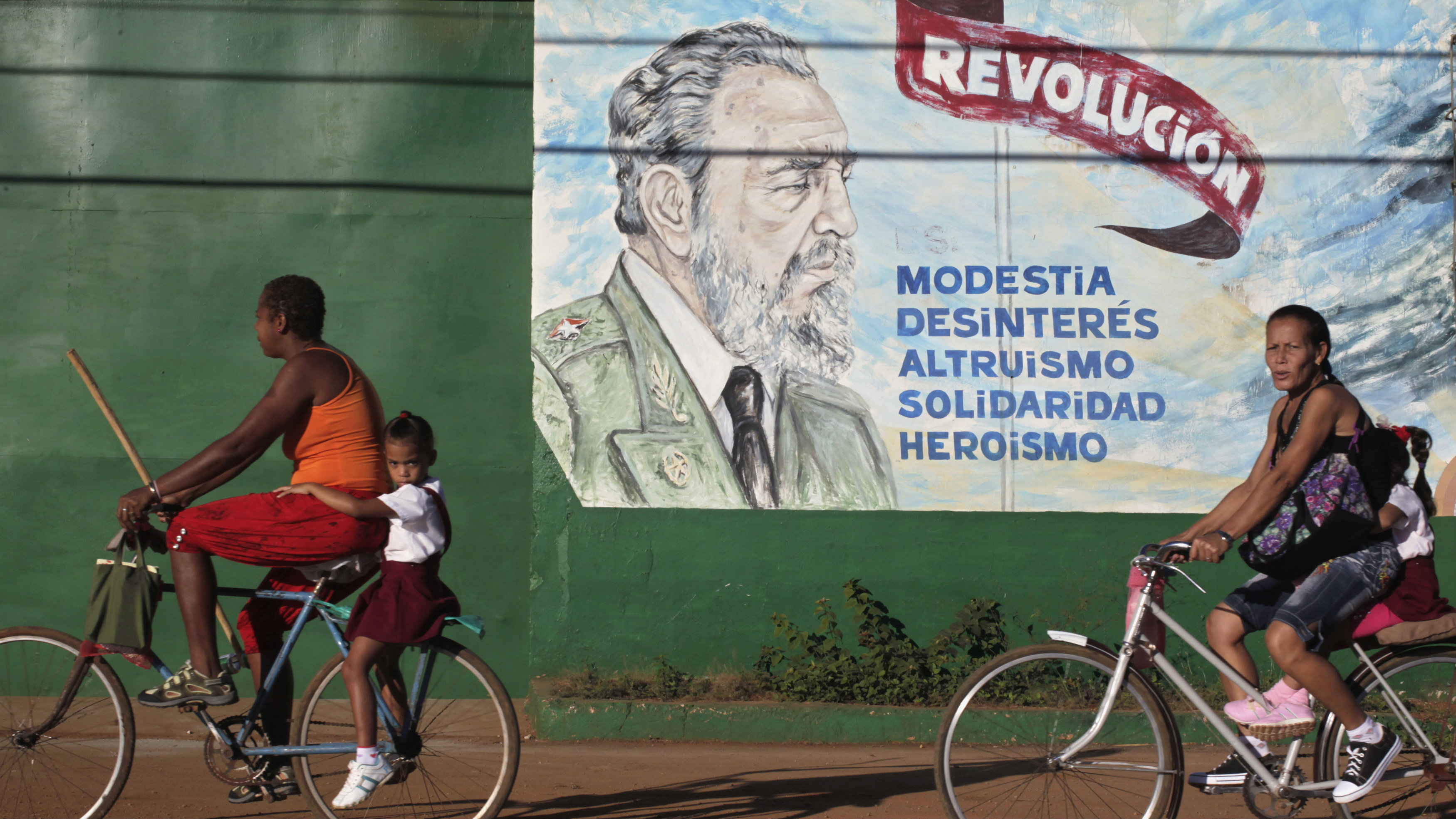 "People ride bicycles in front of graffiti of former Cuban leader Fidel Castro in Artemisa, near Havana November 22, 2013. The words read, ""Revolution is modesty, disinterest, altruism, solidarity, heroism""."