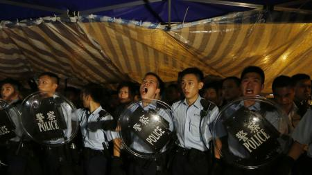 Police officers shout as they instruct the protesters to move to a nearby park at the main roads outside government headquarters in Hong Kong