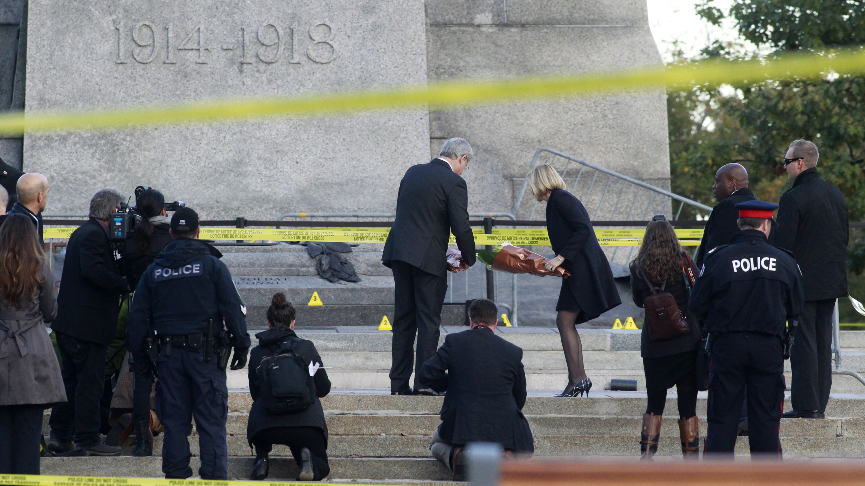 Canada's Prime Minister Stephen Harper and his wife, Laureen Harper, lay flowers at the Canadian War Memorial in downtown Ottawa October 23, 2014. A gunman attacked Canada's parliament on Wednesday, with gunfire erupting near a room where Prime Minister Stephen Harper was speaking, and a soldier was fatally shot at the nearby war memorial, jolting the Canadian capital.