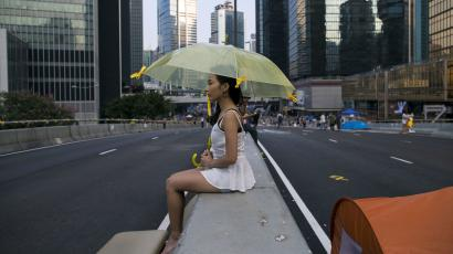 protester of the Occupy Central movement, sits on a divider used by demonstrators to block the main road leading to the financial Central district in Hong Kong October 9, 2014