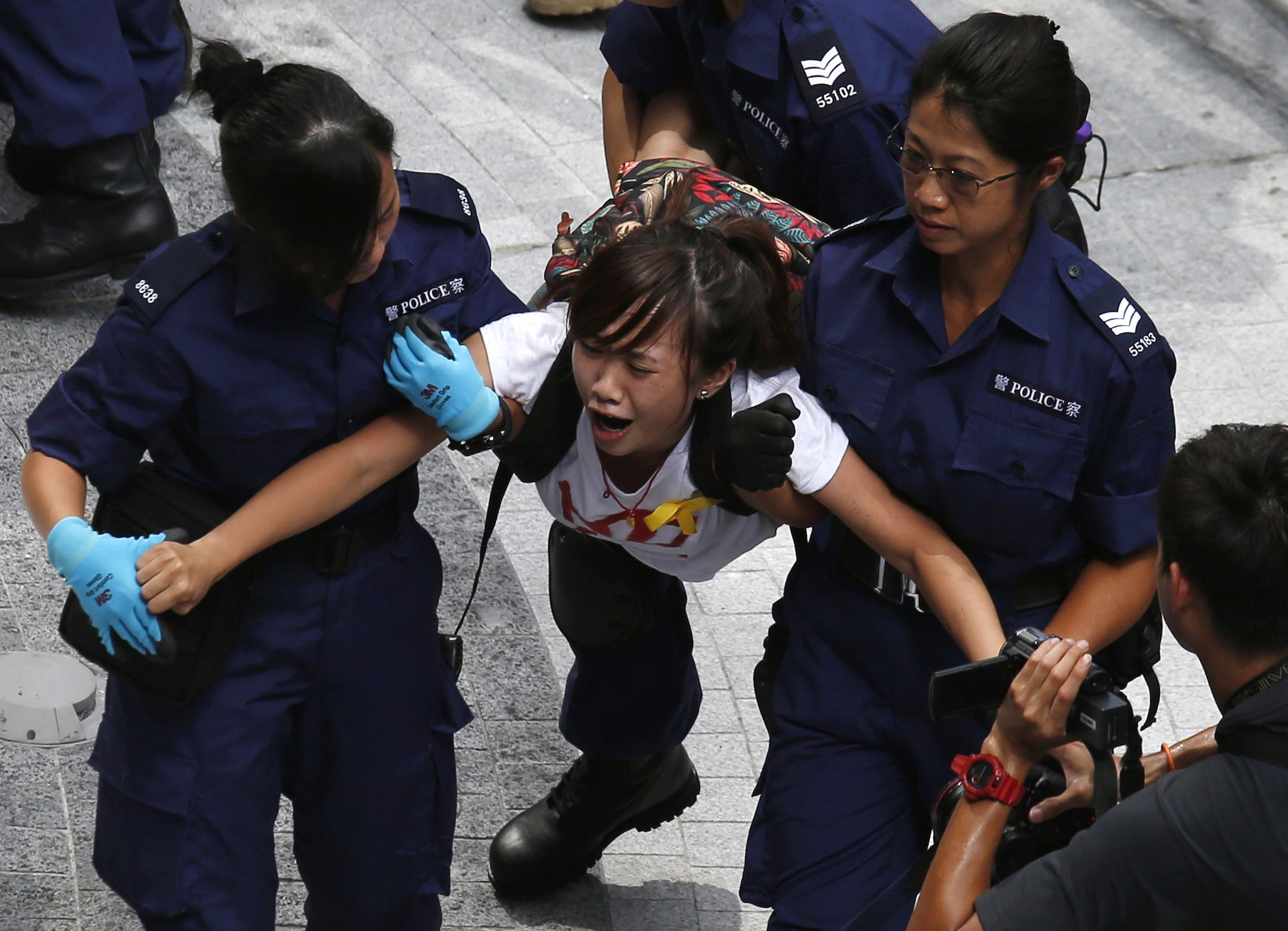 A protester reacts as she is dragged away by police after storming in government headquarters in Hong Kon