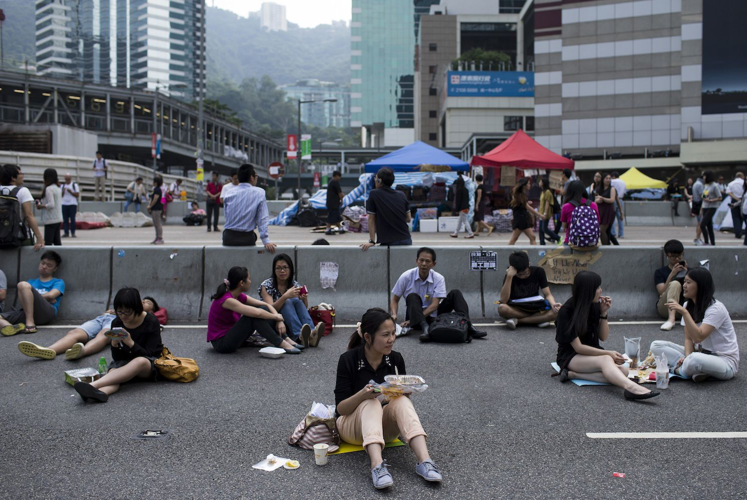 A woman takes her lunch while sitting on a highway, part of an area blocked off by protesters of the Occupy Central movement, in Hong Kong October 7, 2014. Pro-democracy demonstrations in Hong Kong rolled into early Tuesday with hundreds of students remaining camped out in the heart of the city after more than a week of rallies and behind-the-scenes talks showing modest signs of progress. REUTERS/Tyrone Siu (CHINA - Tags: POLITICS CIVIL UNREST FOOD) - RTR497NO