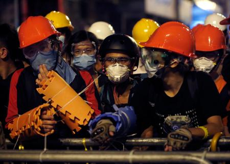 Pro-democracy protesters protect themselves with helmets, masks and foam pads during a standoff with riot police at the Mongkok shopping district