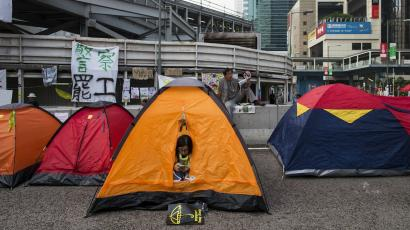 An Occupy Central protester looks her phone in her tent at a protest site in Admiralty near the government headquarters in Hong Kong October 16