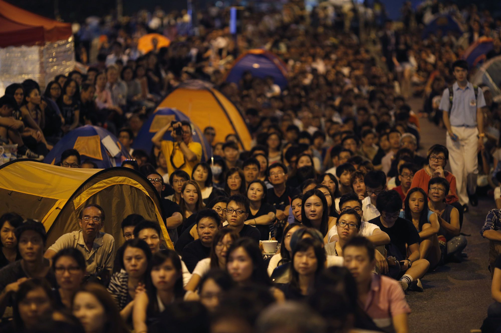 """Pro-democracy protestors watch formal talks between student protest leaders and city officials on a video screen near the government headquarters in Hong Kong October 21, 2014. Hong Kong Chief Executive Leung Chun-ying said on Tuesday there was room for the committee that selects candidates for the territory's 2017 election to be made """"more democratic."""" REUTERS/Carlos Barria (CHINA - Tags: POLITICS CIVIL UNREST BUSINESS) - RTR4AYKF"""