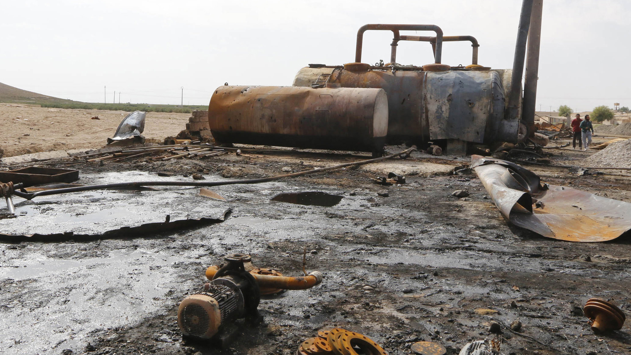 Men walk past damage at an oil refinery and a gas station that were targeted by what activists said were U.S.-led air strikes, in the town of Tel Abyad of Raqqa governorate, near the border with Turkey October 2, 2014.