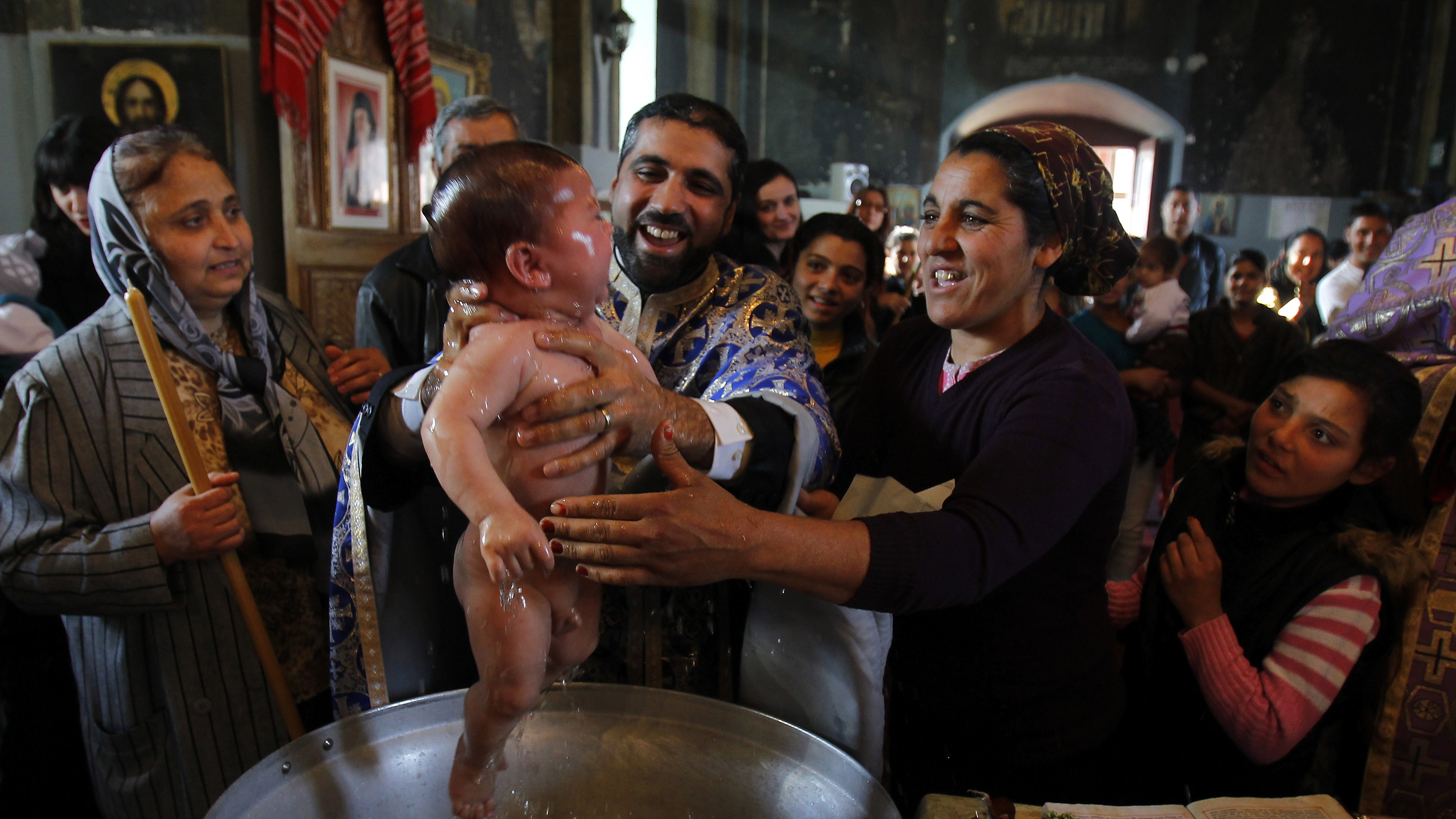 Priest Nicolae Ganga (C), a member of Romania's Roma ethnic minority, baptizes a child during a very rare mass Orthodox baptism ceremony at a church in the Bora neighbourhood in Slobozia, 130 km (81 miles) east of Bucharest November 29, 2012. About 40 Roma ethnic people, aged between one and 57 years, were baptized into the Orthodox Christian faith with Romanians serving as godparents during a very rare mass ceremony in an attempt to strengthen their community ties with the Romanian majority. The Roma people make up the biggest ethnic minority in the European Union, most of them from countries like Romania, Bulgaria and the Czech Republic. There are an estimated 10 million across Europe and one in five lives in Romania.