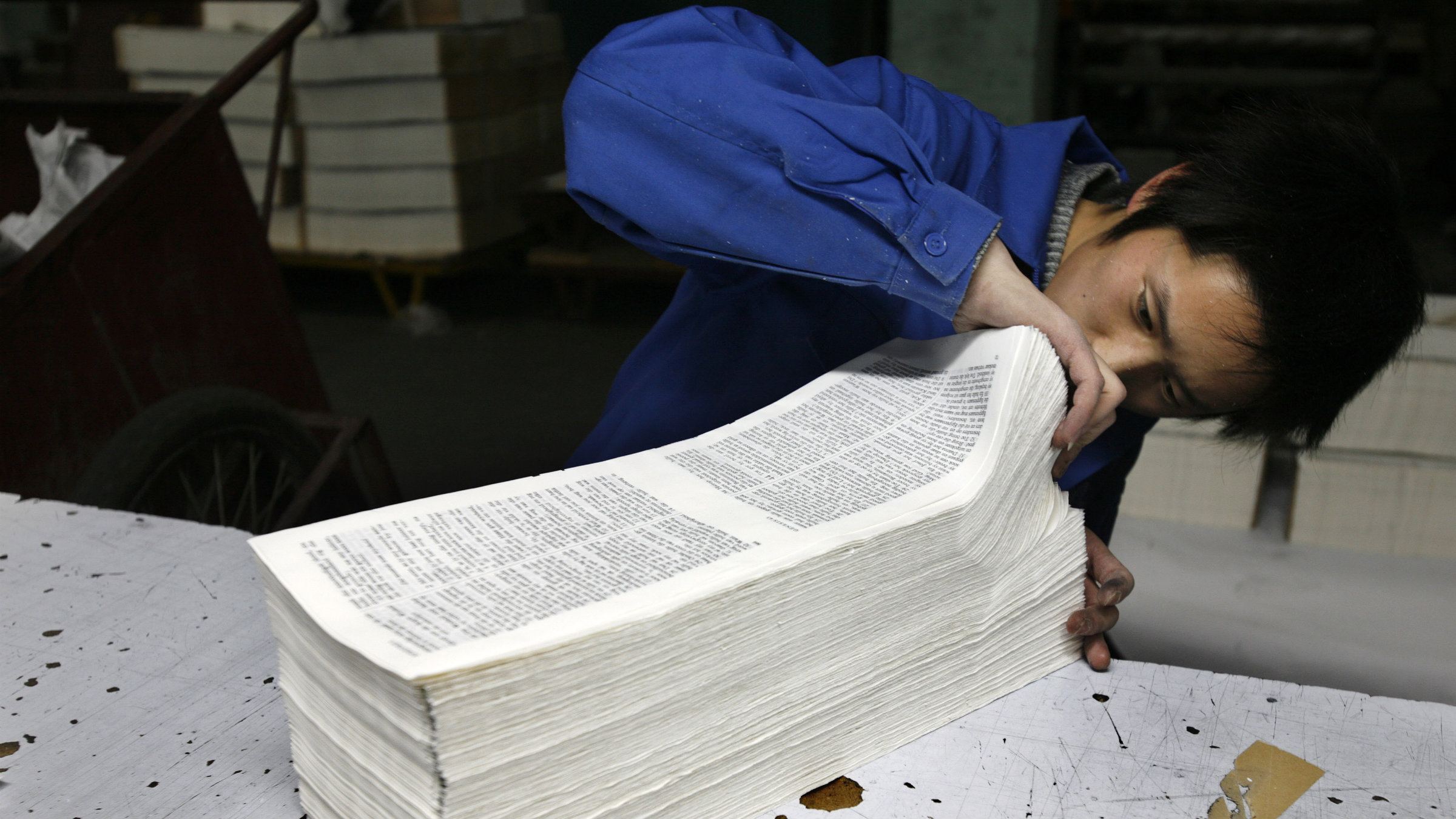 A worker checks for rejects from a batch of newly printed books in the production line at a printing factory.