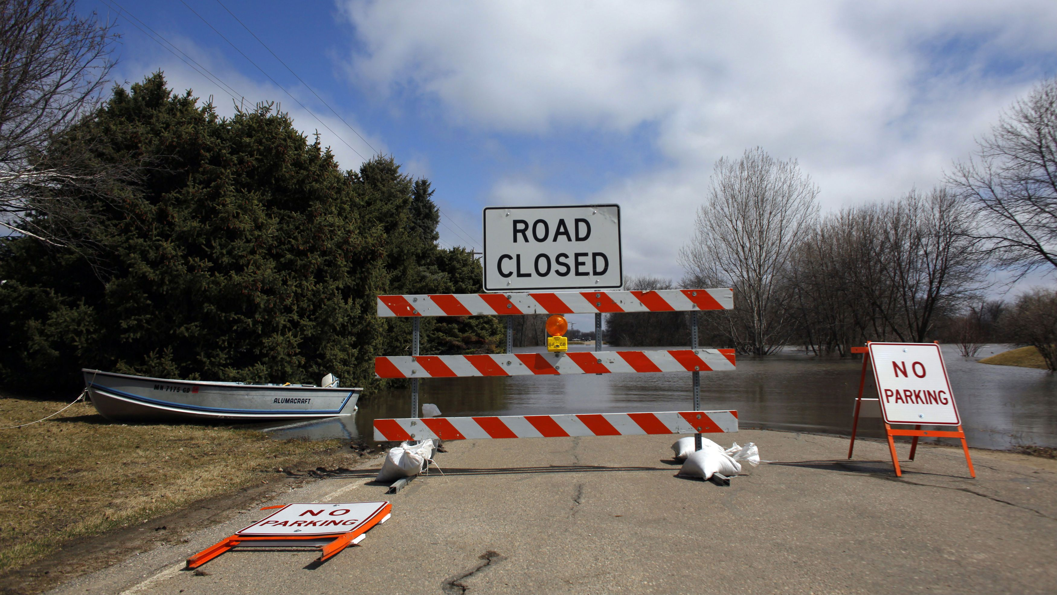 A road covered in water is closed off to traffic in the Burke Addition neighborhood of Grand Forks, North Dakota April 13, 2011. Flooding was spreading out across broad stretches of rural North Dakota and Minnesota on Wednesday and swelling toward a near-record crest in Grand Forks expected within three days. REUTERS/Eric Thayer (UNITED STATES - Tags: ENVIRONMENT)