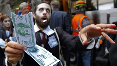 "A demonstrator holds play money while dressed as a ""corporate zombie"" as he walks with others taking part in an Occupy Wall Street protest in lower Manhattan."