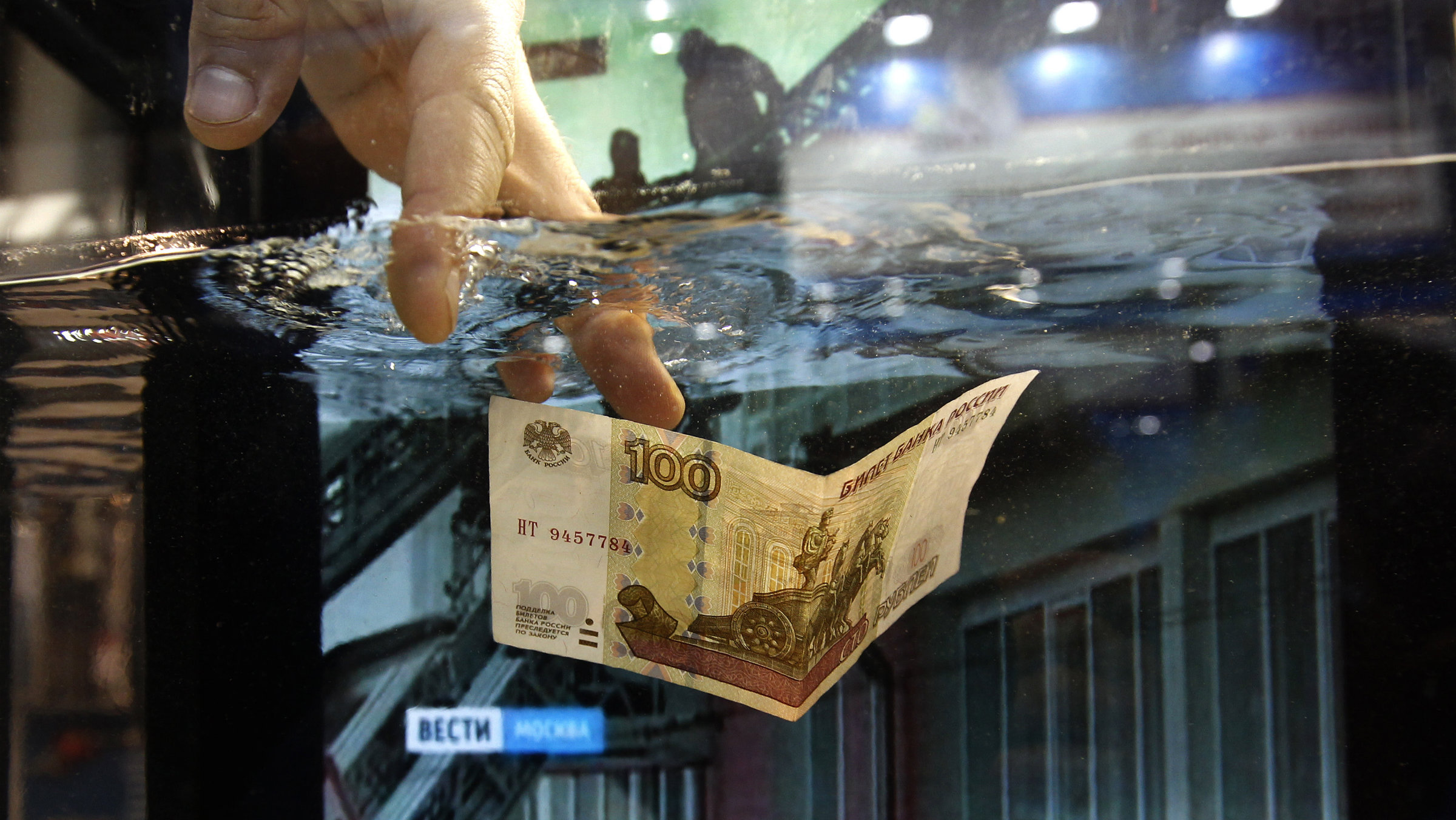 A 3M Co company representative sinks a 100 rouble banknote in a container of fire suppression fluid during a presentation at the Security and Safety International Forum in St. Petersburg.