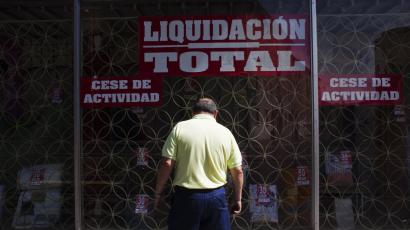 A man window shops at a store going out business in Madrid.