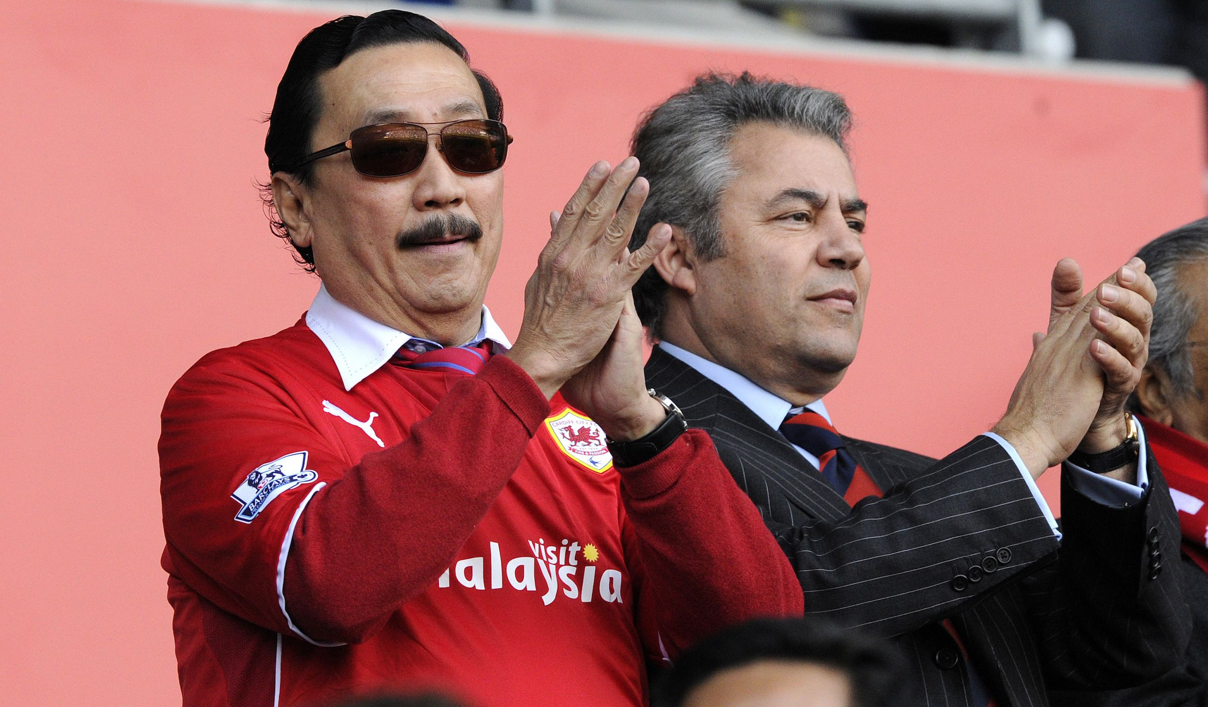 """Cardiff City's owner Vincent Tan (L) applauds with Club Chairman Mehmet Dalman during their English Premier League soccer match against Fulham at Cardiff City Stadium in Cardiff, Wales, March 8, 2014. REUTERS/Rebecca Naden (BRITAIN - Tags: SPORT SOCCER) NO USE WITH UNAUTHORIZED AUDIO, VIDEO, DATA, FIXTURE LISTS, CLUB/LEAGUE LOGOS OR """"LIVE"""" SERVICES. ONLINE IN-MATCH USE LIMITED TO 45 IMAGES, NO VIDEO EMULATION. NO USE IN BETTING, GAMES OR SINGLE CLUB/LEAGUE/PLAYER PUBLICATIONS. FOR EDITORIAL USE ONLY. NOT FOR SALE FOR MARKETING OR ADVERTISING CAMPAIGNS - RTR3G8M9"""