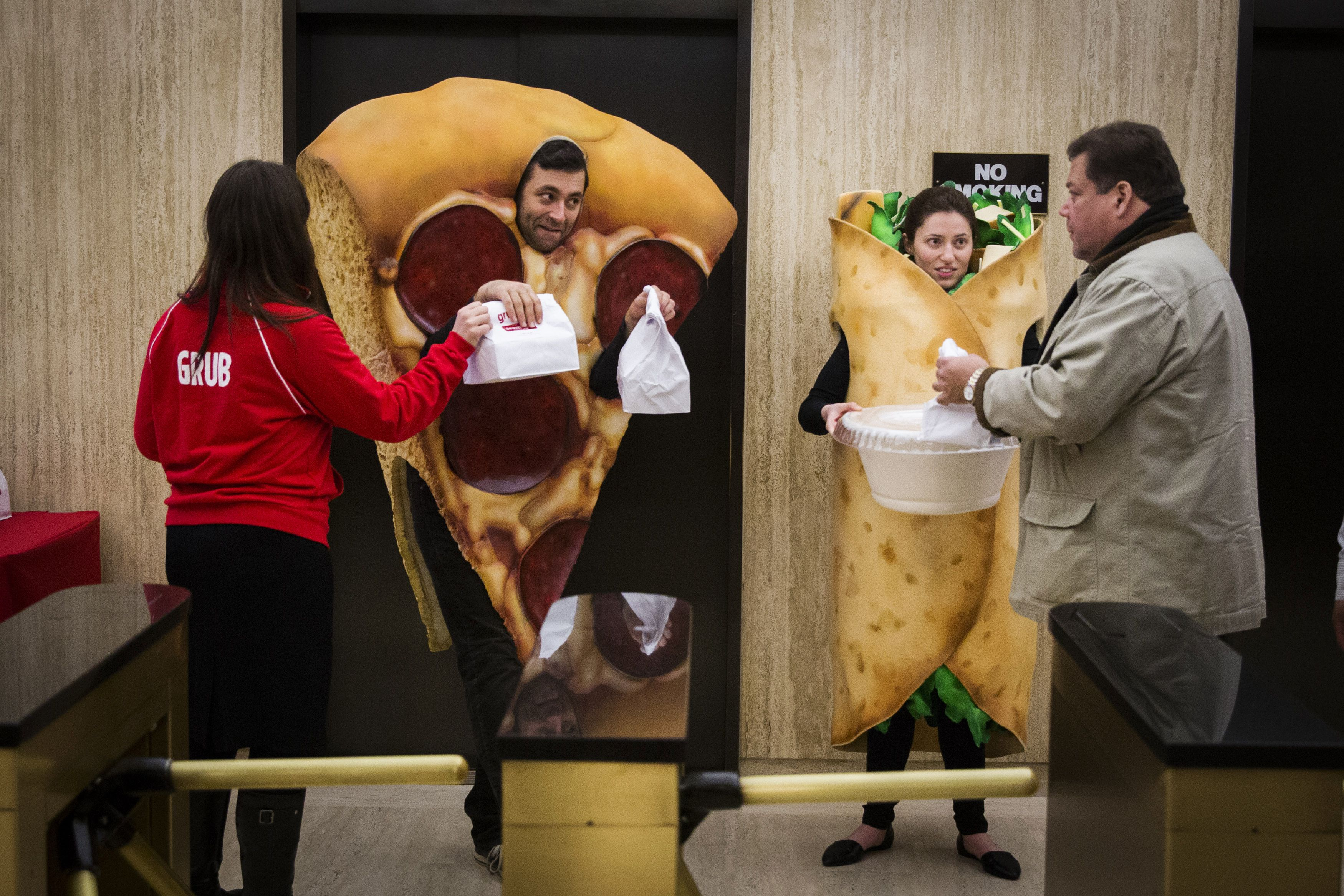 People dressed in food-themed costumes give away donuts to people headed to the floor of the New York Stock Exchange to celebrate the IPO of GrubHub, in New York April 4, 2014. Shares of GrubHub Inc, the biggest U.S. online food-delivery service, rose as much as 57 percent in its market debut as investors scrambled for a piece of the fast-growing consumer internet company.  REUTERS/Lucas Jackson (UNITED STATES - Tags: BUSINESS FOOD) - RTR3JYXC
