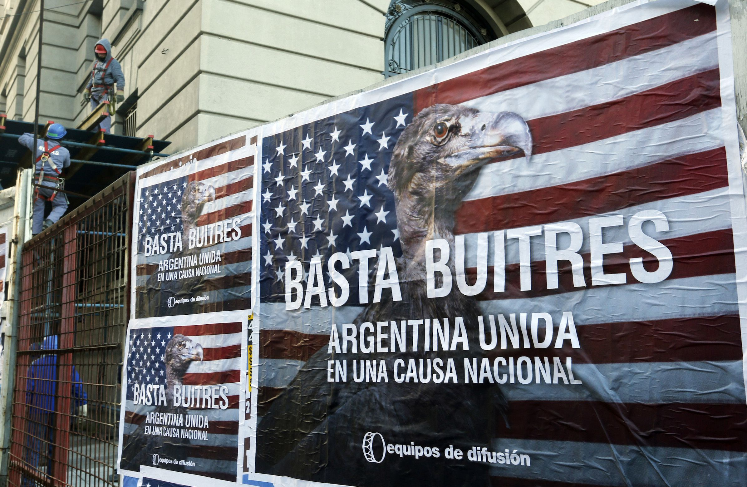 """Construction workers work near posters that read """"Enough vultures, Argentina united for a national cause"""" in Buenos Aires June 18, 2014. Argentina is taking steps to place its restructured debt under local law so it can continue making payments despite a string of adverse U.S. court rulings, Economy Minister Axel Kicillof said on Tuesday as fears of default increased. Under the move, Argentina would swap bonds that are governed by U.S. law for those governed by Argentine law, meaning they would no longer be subject to the U.S. courts.   REUTERS/Enrique Marcarian (ARGENTINA - Tags: BUSINESS POLITICS CRIME LAW) - RTR3UG0T"""