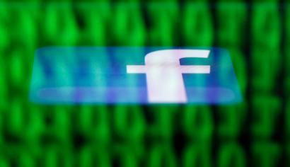 A Facebook logo on an Ipad is reflected among source code on the LCD screen of a computer, in this photo illustration taken in Sarajevo June 18, 2014. Ireland's High Court on Wednesday asked the European Court of Justice (ECJ) to review a European Union-U.S. data protection agreement in light of allegations that Facebook shared data from EU users with the U.S. National Security Agency. REUTERS/Dado Ruvic (BOSNIA AND HERZEGOVINA - Tags: CRIME LAW BUSINESS POLITICS) - RTR3UH6G