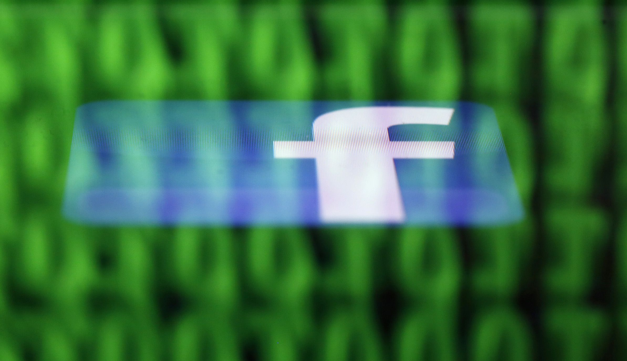 A Facebook logo on an Ipad is under the source code on the LCD Screen shot of a computer reproduced in this photo illustration in Sarajevo on June 18, 2014. Ireland's Supreme Court has questioned the European Court of Justice (ECJ) on Wednesday to review a European Union-US privacy agreement given the allegations that Facebook receives data from EU Users shared with the US National Security Agency REUTERS / Dado Ruvic (BOSNIA AND HERZEGOVINA - Tags: CRIME LAW BUSINESS POLITICS) - R TR3UH6G