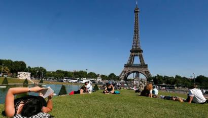 A woman reads a book as she rests in a public garden near the Eiffel Tower on a hot summer day in Paris