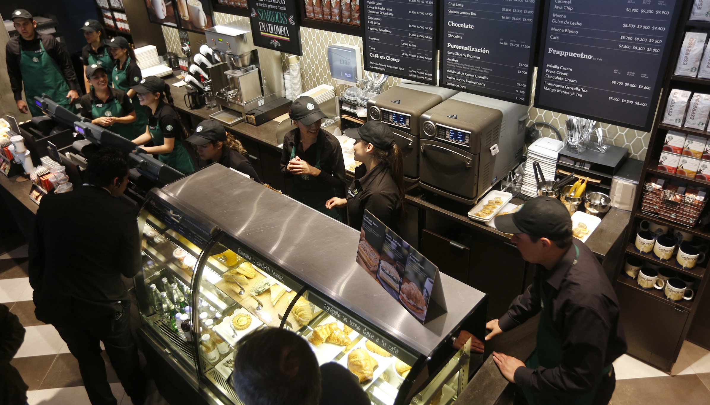 People are seen at Starbuck's first Colombian store at 93 park in Bogota July 16, 2014. Starbucks Corp opened its first shop in Colombia on Wednesday, 43 years after the world's biggest coffee chain first started buying beans from the country famous for its premium arabica coffee named after fictional coffee farmer Juan Valdez. REUTERS/John Vizcaino (COLOMBIA - Tags: BUSINESS) - RTR3YXSO
