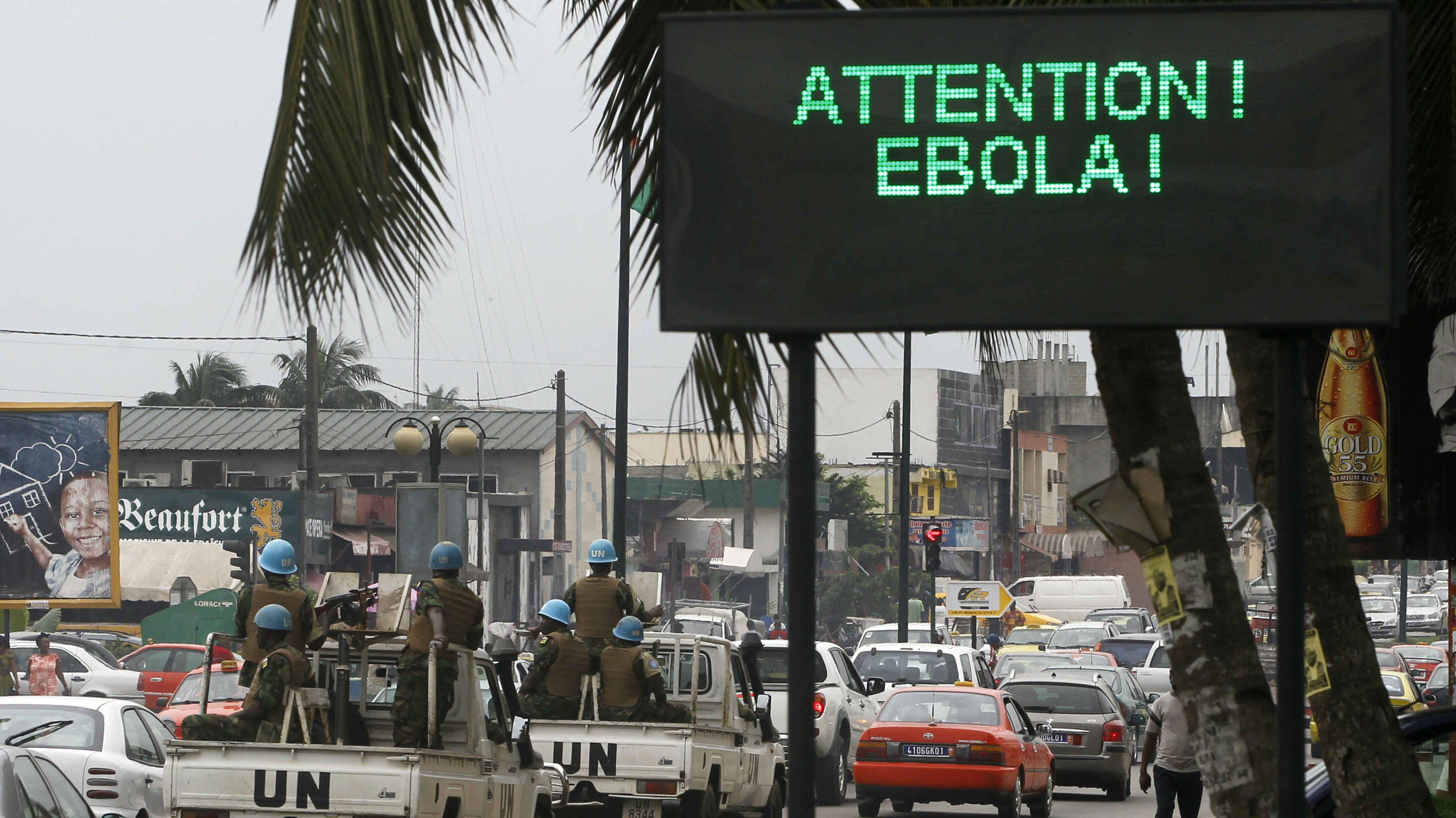 A U.N. convoy of soldiers passes a screen displaying a message on Ebola on a street in Abidjan August 14, 2014. The world's worst outbreak of Ebola has claimed the lives of 1,069 people and there are 1,975 probable and suspected cases, the vast majority in Guinea, Liberia and Sierra Leone, according to new figures from the World Health Organisation (WHO). Ivory Coast has recorded no cases of Ebola. REUTERS/Luc Gnago (IVORY COAST - Tags: HEALTH TRANSPORT TPX IMAGES OF THE DAY)